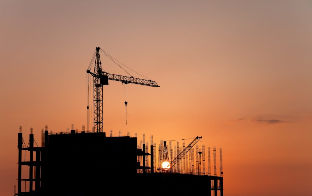 Construction cranes and concrete structure at sunset